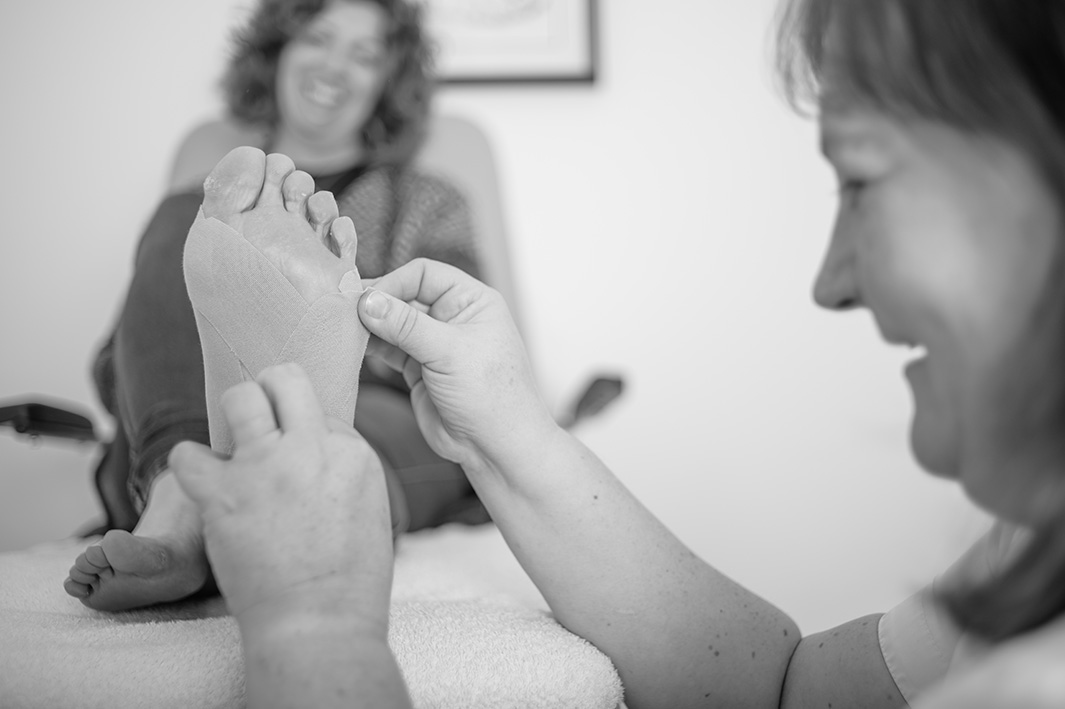 jennifer maxwell of the dalkey podiatry clinic strapping up a patient's foot